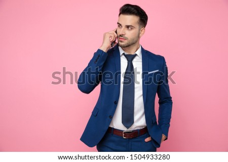 smart casual man wearing navy blue suit, talking on the phone, holding hand in pocket, looking to side and standing on pink background in studio #1504933280