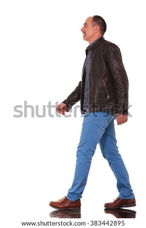 smart casual mature man in leather jacket walking in isolated studio background while looking away from the camera #383442895