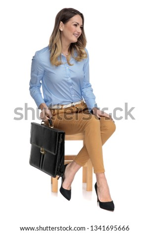 smart casual woman holding her suitcase while sitting on a wooden stool, looking at a side, on a light background, full body picture #1341695666