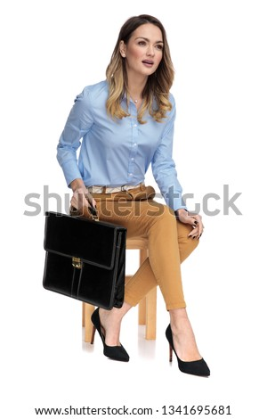 smart casual woman holding her suitcase while sitting on a wooden stool, looking at a side, on a light background, full body picture #1341695681