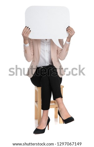 smart casual woman holds speech bubble in front of her face while sitting with feet folded on white background, #1297067149