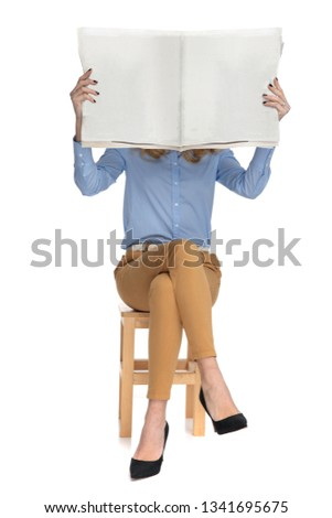smart casual woman reading the newspaper sits on wooden chair on white background, full length picture #1341695675
