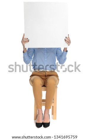 smart casual woman sitting on stool holds advertisement on white background #1341695759