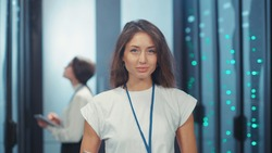 Smart cheerful woman server specialist working in data center. Indoor portrait of smiling female administrator standing in rack server corridor computer security.