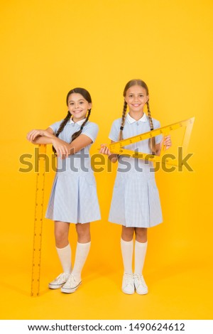 smart children at stem lesson. girls love geometry. old school. modern education. happy friends in retro uniform. vintage kid fashion. back to school. small girls hold math tools. STEM disciplines.
