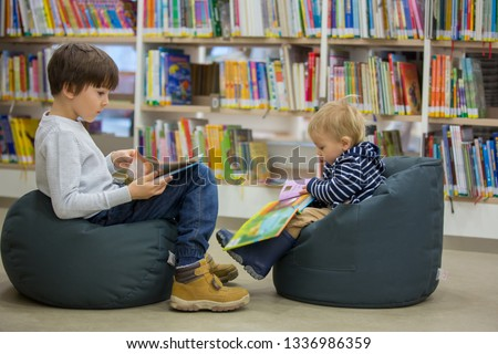 Smart children, boy brothers, toddler and school kid, educating themselves in a library, reading books and looking at pictures