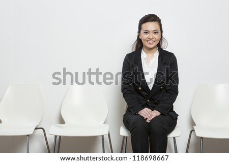 Smart Chinese business woman waiting for a job interview. Sitting on a row of chairs. - stock photo