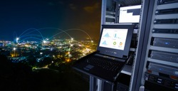 smart city concept. monitor show graph information of network traffic and status of device in the server room of the data center and blending with cityscape panorama of Phuket city, Thailand at night
