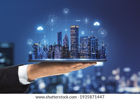 Smart city concept with real skyscrapers layout with glowing digital cloud technology icons on digital tablet screen that carrying businessman hand on blurry megapolis city background