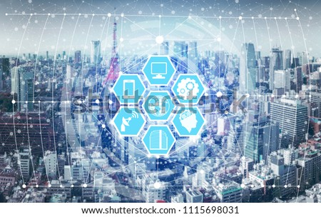 Smart city wireless communication network with graphic showing concept of internet of things (IOT) and information communication technology (ICT) against modern city buildings in the background. #1115698031