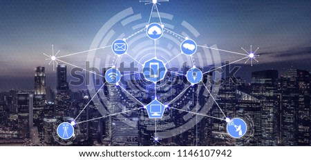 Smart city wireless communication network with graphic showing concept of internet of things (IOT) and information communication technology (ICT) against modern city buildings in the background. #1146107942