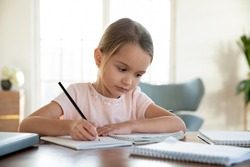Smart concentrated small 7s Caucasian girl child sit at desk at home study distant do homework with textbooks. Pensive little kid handwrite learn preparing school task assignment. Education concept.