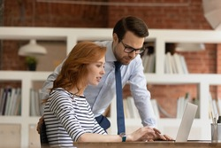 Smart confident male team leader supervisor boss helping new female employee with corporate software, working together in modern office. Happy professional managers developing online sales strategy.