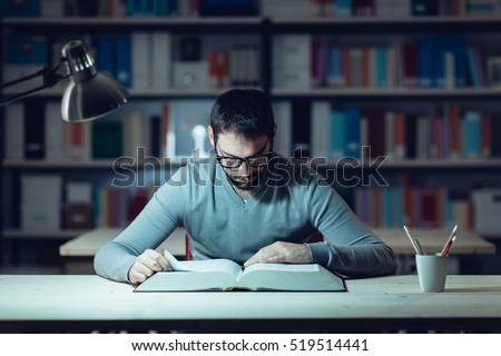 Shutterstock Smart confident young man studying late at night, he is sitting at desk and reading a book, knowledge and learning concept