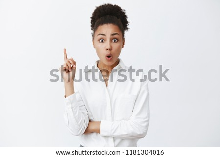 Smart, creative african-american lady entrepreneur in white-collar shirt, raising index finger in eureka gesture, folding lips, adding great suggestion during team meeting in office, having discussion