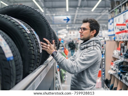 Smart customer taking new tires in the supermarket for buying. He looks happy. Big shopping mall with car goods.