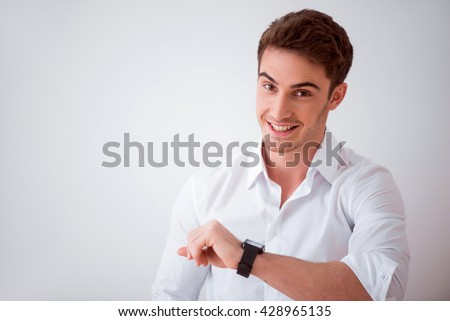 Smart device. Joyful delighted smiling man using his smart watch  while standing isolated o white background  Stockfoto ©
