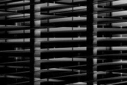 Smart double exposure photo of backlit industrial interior in the darkness. Modern architecture detail. Abstract black and white architectural background with grid structure.
