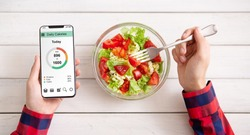 Smart eating and diet planning concept. Man eating vegetable salad and counting calories on mobile application, top view