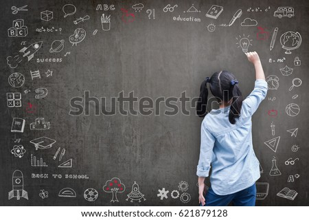 Smart educated Asian school girl kid student drawing doodle and writing on black classroom chalkboard background for national back to school month, educational inspiration and world literacy concept #621879128