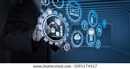 Smart factory and industry 4.0 and connected production robots exchanging data with internet of things (IoT) with cloud computing technology.business man with an open hand as showing something concept