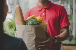 smart food delivery service man in red uniform handing fresh food to recipient and young woman customer receiving order from courier at home, express delivery, food delivery, online shopping concept