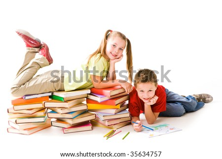 Smart girl lying on top of book piles with cute schoolboy drawing near by