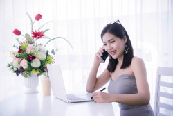 smart girl's using smart phone and working on laptop ,happy time on work, smile and laughing time work , workingwomen get think about work online selling