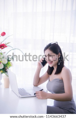 smart girl's using smart phone and working on laptop ,happy time on work, smile and laughing time work , workingwomen get think about work