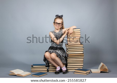 smart girl with a stack of books. Girl with glasses reading a book