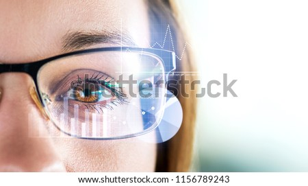 Smart glasses and augmented reality concept. Woman wearing modern spectacles with futuristic screen. Virtual technology. Close up of eye surrounded by business statistics and analytics. Future vision.