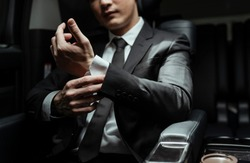 Smart guy on black suit preparing for a meeting in a car.