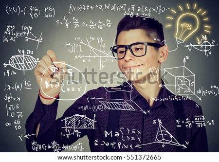 Smart guy writing high school maths and science formulas on blackboard