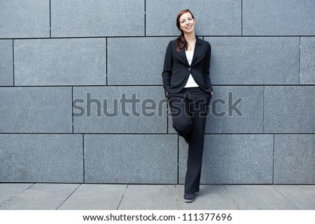 Smart happy business woman leaning on wall in the city