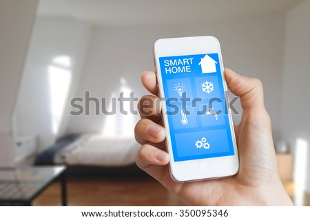 Smart home automation app on smartphone hold by female hand with home interior in background