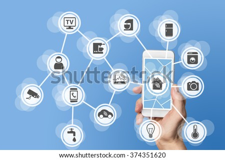 Smart home automation concept with hand holding modern smart phone to control devices like a thermostat and sensor via the world wide web