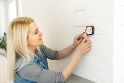 Smart home digital thermostat touch screen woman touching touchscreen to adjust temperature of heating in living room wall