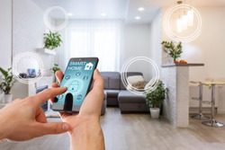 Smart home technology interface on smartphone app screen with augmented reality (AR) view of internet of things (IOT) connected objects in the apartment interior, person holding device