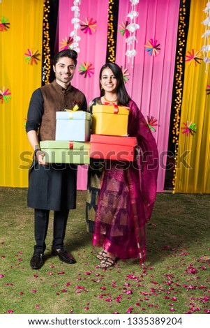 c8aeaa5a53 Smart Indian couple standing with gift boxes on Diwali festival or wedding  ceremony #1335389204 · south indian festival onam ...
