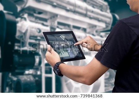 Smart industry control concept.Hands holding tablet on blurred automation machine as background #739841368