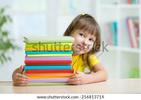 Smart kid girl preschooler with books in primary school