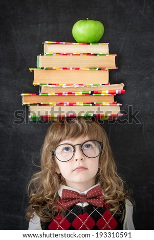 Smart kid in library. Schoolchild with textbooks and green apple against blackboard. Education concept