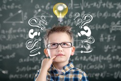 Smart kid with lightbulb. Brainstorming and idea concept. Little student boy on chalkboard background