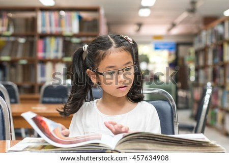 Smart little asian child girl w/ eyeglasses reading book school background: Lovely cute young female student kid opening flipping book in archive resource collection room: National library lover month