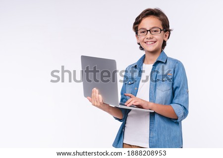 Smart little boy with laptop in casual clothes isolated over white background