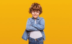 Smart little ginger nerd boy with curly hair wearing denim outfit and round glasses standing with arms crossed against yellow background and looking at camera