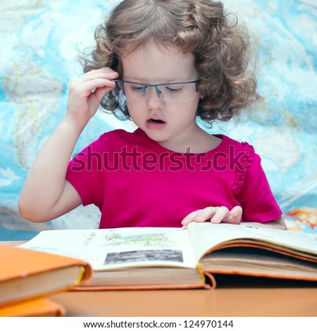 Smart little girl with glasses reading a book, square image