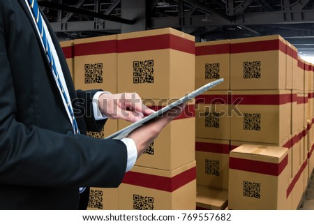 Smart logistic industry 4.0 , QR Codes Asset warehouse and inventory management supply chain technology concept. Businessman using tablet and group of boxes in storehouse can check product inside. #769557682