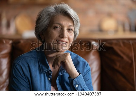 Smart look. Profile picture of attractive old latin lady of retirement age enjoy self beauty care look at camera with smile. Beautiful elegant elderly female posing for portrait on cozy sofa at home