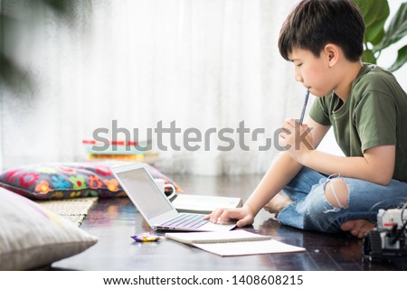 Smart looking Asian preteen boy sit crossed legs, holding pen against his lips, thinking and looking at computer notebook at home due to Covid-19 pandemic and social distancing measures. New normal.